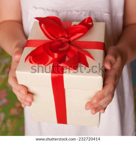 Kids hands holding a gift close-up. New Year, Christmas, mother's day, father's day, holiday concept. - stock photo