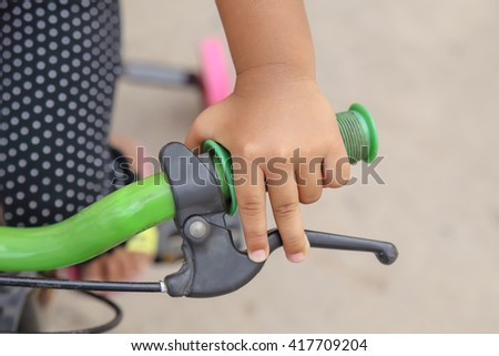 Kids hands holding handle of old bicycle - stock photo