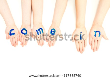 Kids hands with come in welcome painted on them. On white. - stock photo