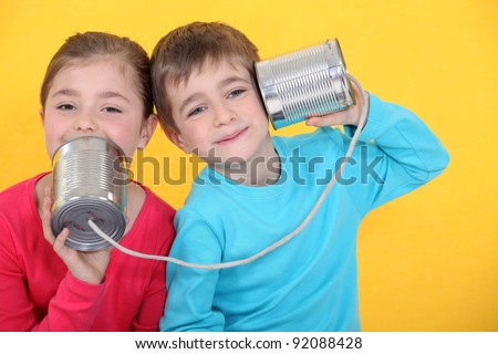 Kids having a phone call with tin cans on yellow background - stock photo