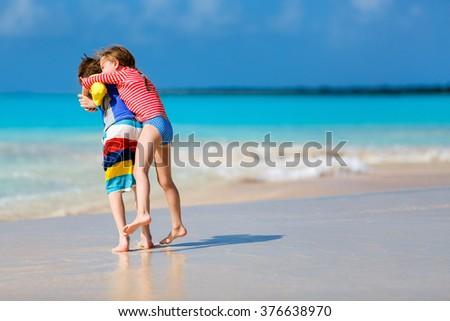 Kids having fun at tropical beach during Caribbean summer vacation playing together at shallow water - stock photo