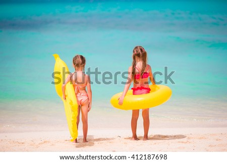 Kids having fun at tropical beach playing together at shallow water - stock photo