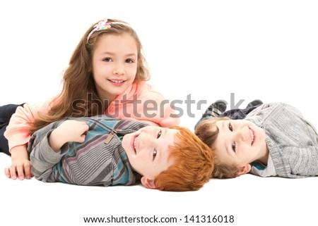 Kids having fun lying on floor together. On white. - stock photo