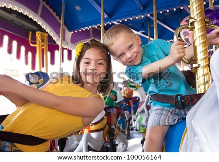 Kids having fun on a carnival Carousel - stock photo