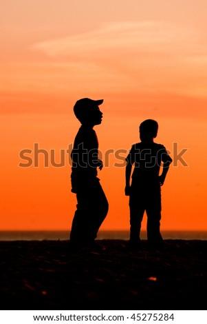 Kids having fun on the beach playing football - stock photo