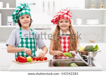 Kids helping in the kitchen - washing and slicing vegetables for a meal