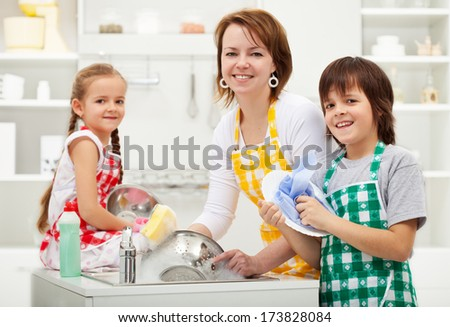 Kids helping their mother in the kitchen - washing the dishes together - stock photo