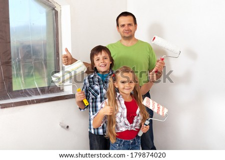 Kids helping there father painting- holding paint rollers - stock photo