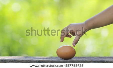 Kids holding a Egg on wooden table with shallow DOF green background