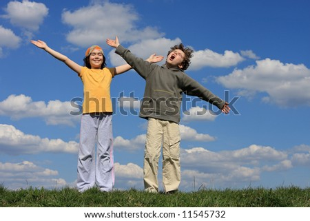 Kids holding arms up against blue sky - stock photo