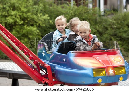 Kids in a flying object on the fancy fair - stock photo