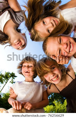 Kids in a huddle having fun and looking down