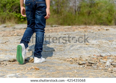 Kids in blue jean walking through the rough rocky land in the day time with strong sunlight. focus on shoe.