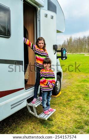 Kids in camper (rv), family travel in motorhome on vacation  - stock photo