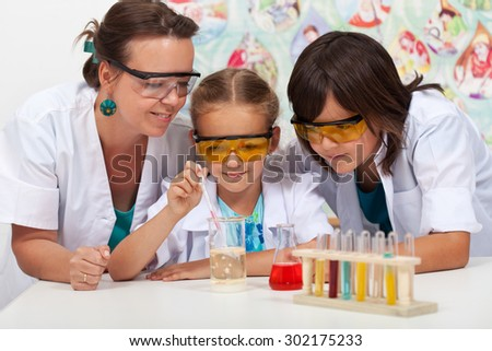 Kids in chemistry class with their teacher - doing a simple experiment
