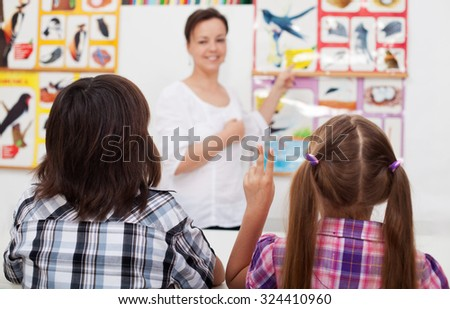 Kids in elementary science class with their teacher - closeup, focus on the child hand - stock photo