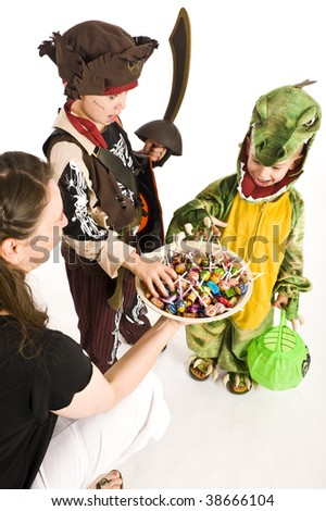 Kids in Halloween costumes playing trick or treat and asking for sweets. - stock photo