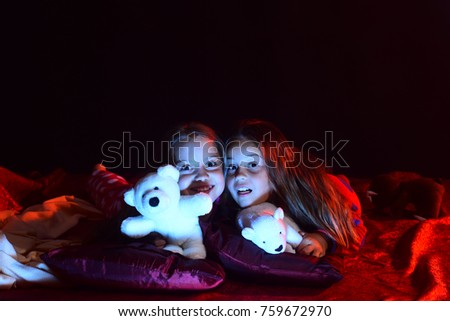 Kids in pajamas lie with teddy bears on dark background. Schoolgirls have pajama party. Girls and leisure concept. Children with surprised faces lie on bed.