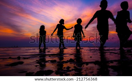 kids in silhouette play at beach during sunset - stock photo