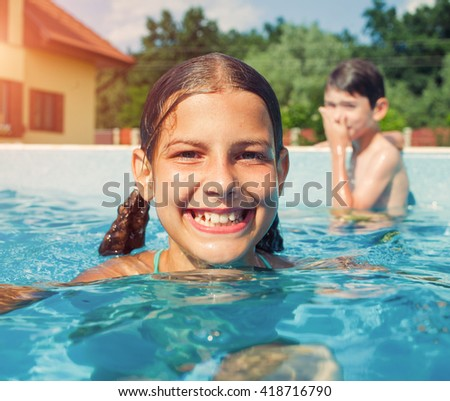 Kids in swimming pool. Girl swim outdoors.