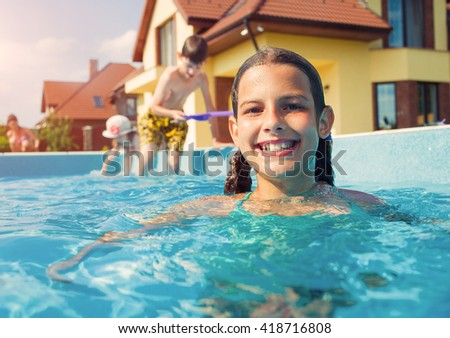 Kids in swimming pool. Girl swim outdoors.  - stock photo
