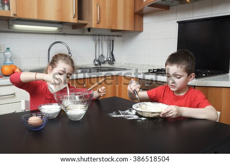 kids in the kitchen making dough mixing flour, milk, eggs in a glass bowl  - stock photo