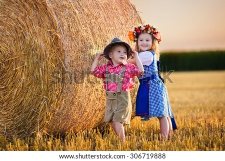 Kids in traditional Bavarian costumes in wheat field. German children eating bread and pretzel during Oktoberfest in Munich. Brother and sister play at hay bales during autumn harvest time in Germany - stock photo