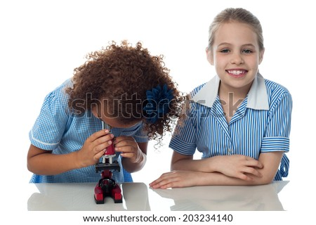Kids in uniform using microscope in lab - stock photo