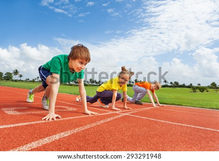 Kids in uniforms on bended knee ready to run - stock photo