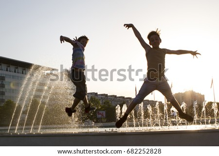 kids jumping and having fun near a fountain