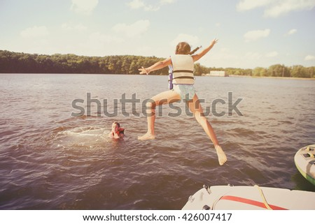 Kids jumping off a boat into the lake. Vintage Instagram effect. Some motion blur