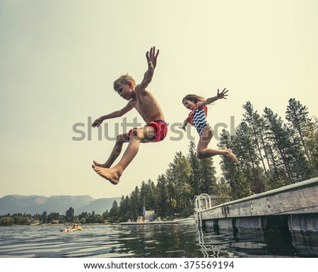 Kids jumping off the dock into a beautiful mountain lake. Having fun on a summer vacation at the lake with friends - stock photo