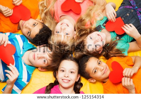 Kids laying in circle with hearts in their hands smiling, boys and girls with diversity - stock photo