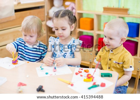 kids learning arts and crafts in kindergarten - stock photo
