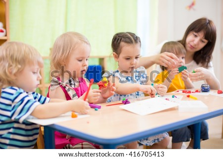 kids learning arts and crafts in kindergarten with teacher
