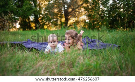 Kids lie on the blanket laid on grass for rest in the open air. Beautiful kids - the brother and the sister