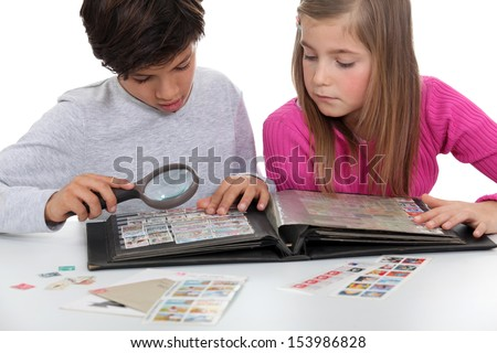 Kids looking at a stamp album - stock photo