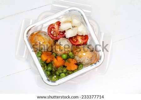 Kids lunch box: stewed peas and carrots, turkey meat balls, cherry tomatoes and goat cheese - stock photo