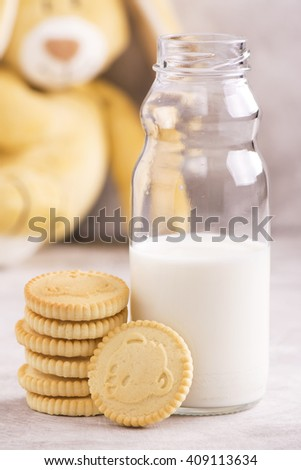 Kids lunch concept: milk in bottle and crispy cookies with funny bunny over stone background - stock photo