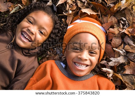 Kids lying on leaves - stock photo