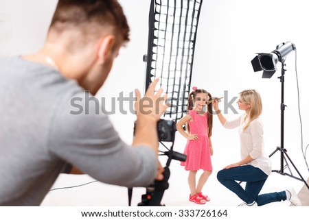 Kids makeup. Small girl stands with her hand on the side while plain make up is being applied by professional.  - stock photo