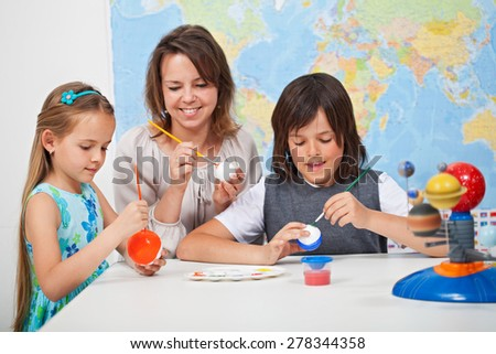 Kids making a scale model of the solar system in science class - helped by their teacher - stock photo