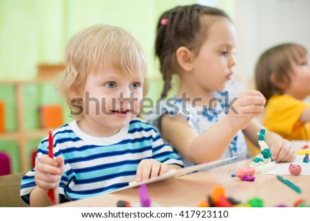kids making arts and crafts in day care centre together - stock photo