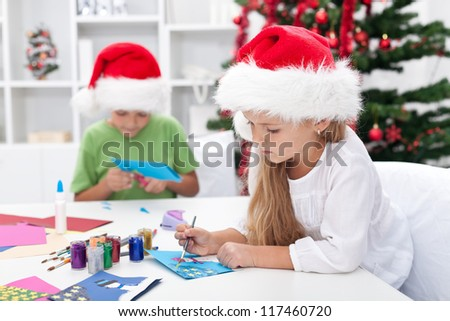 Kids making christmas or seasonal greeting cards - stock photo