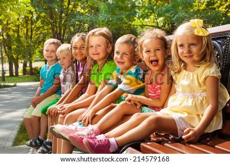 Kids on summer park bench - stock photo