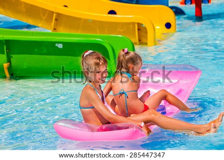 Kids on water slide at aquapark. Summer holiday outdoor
