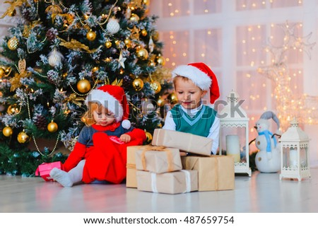 Kids opening christmas presents in decorated living room