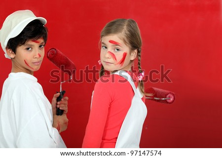 Kids painting a wall in red - stock photo