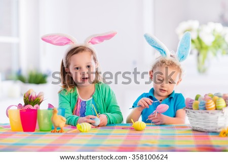 Kids painting colorful eggs. Children paint and decorate Easter egg. Toddler kid and preschooler child play indoors in spring. Decorated home with spring tulip flowers. Family celebrating Easter.