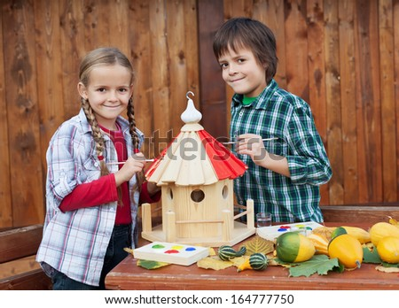 Kids painting the bird house preparing for winter - environmental awareness concept - stock photo